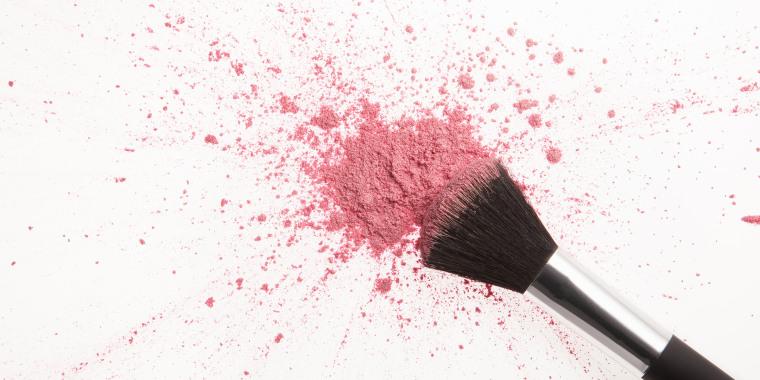 Makeup brush and pink blush powder splatter