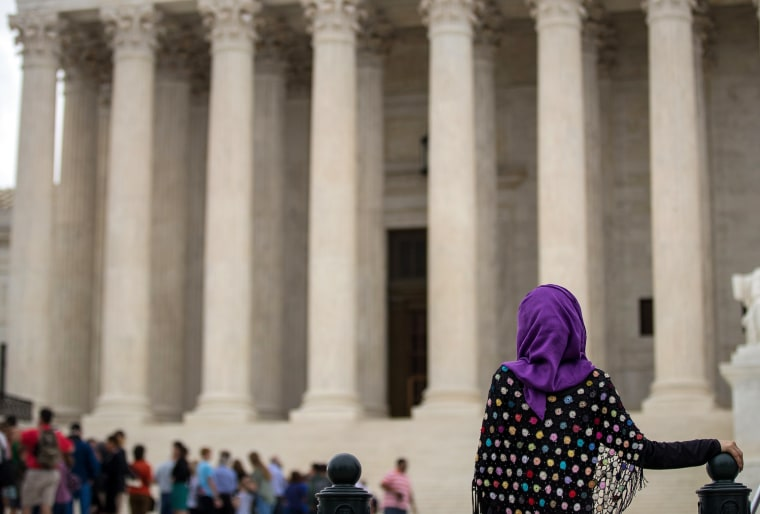 Image: A woman wearing a hijab stands outside the U.S. Supreme Court in Washington