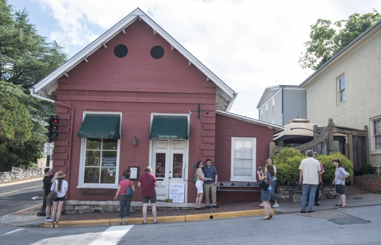 Passersby gather to take photos in front of the Red Hen Restaurant in Lexington, Virginia.
