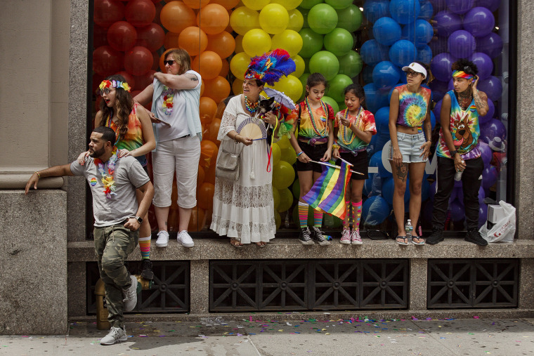 Image: People watch as revelers march during the annual Pride Parade in New York
