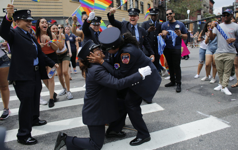 Image: Members of the New York City Fire Department cheer as a couple gets engaged at the annual Pride Parade