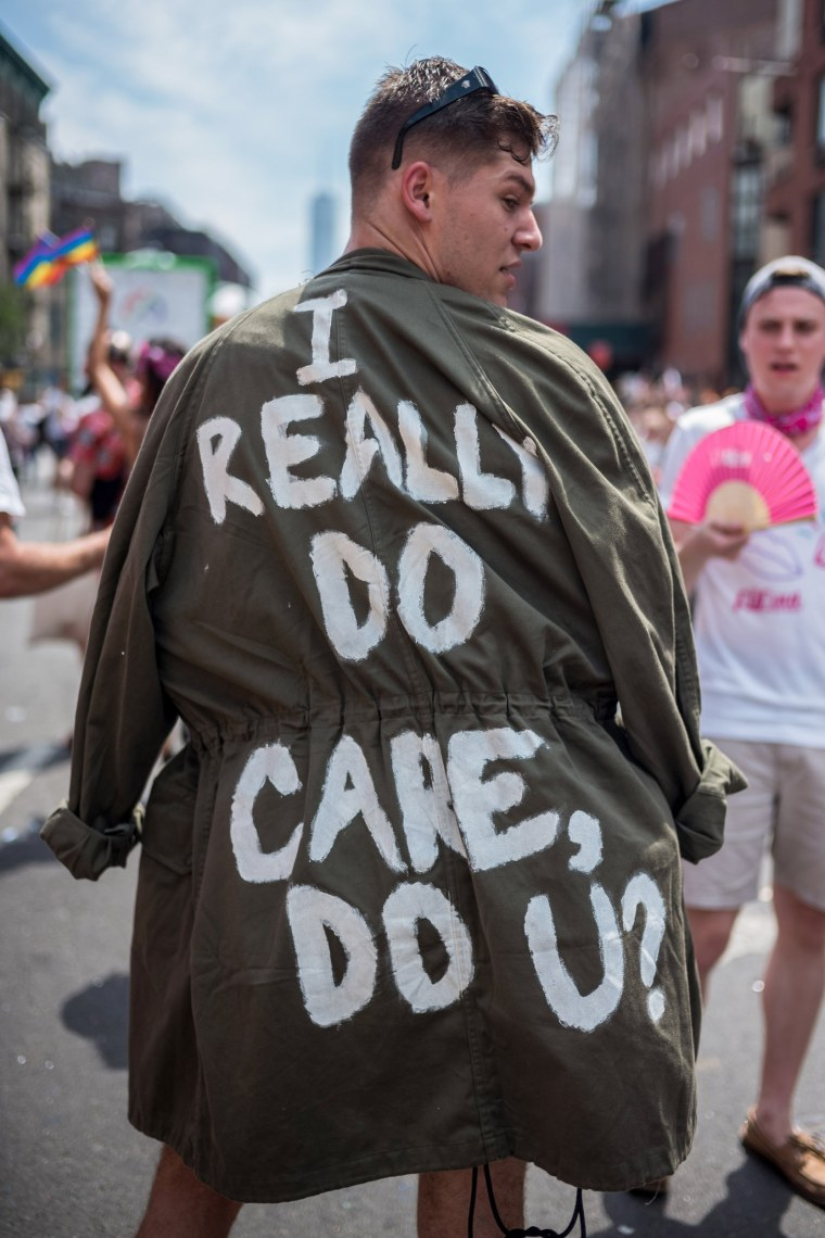 """Image: A participant wears a a jacket that reads """"I really do care, do u?"""" during the Pride parade in New York"""