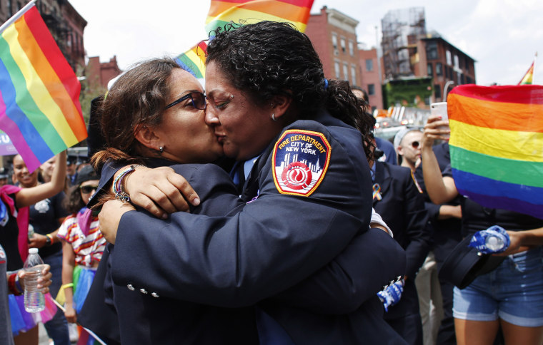 Image: Tracy Bermudez, left, and Tayreen Bonilla kiss after Bermudez proposed during the Pride parade