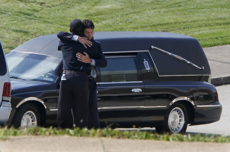 Image: A person attending the funeral for Antwon Rose Jr. embraces a police officer
