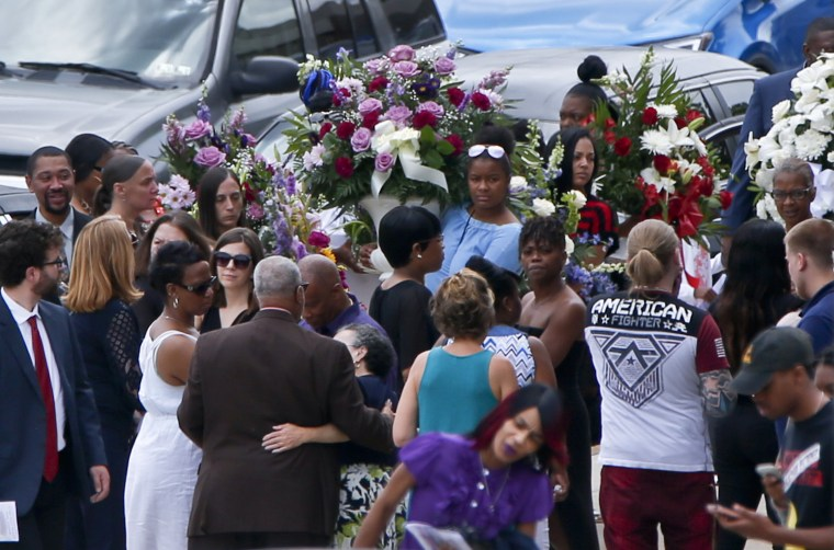 Image: People carry flowers as they leave Antwon Rose Jr.'s funeral