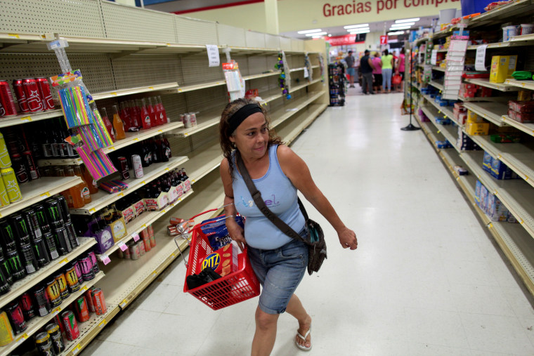 Image: A woman looks for food along an empty area of a supermarket following Hurricane Maria in San Juan, Puerto Rico
