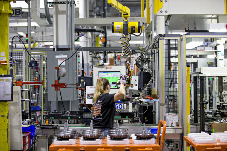 Image: An employee moves a flywheel assembly at the Harley-Davidson Inc. facility