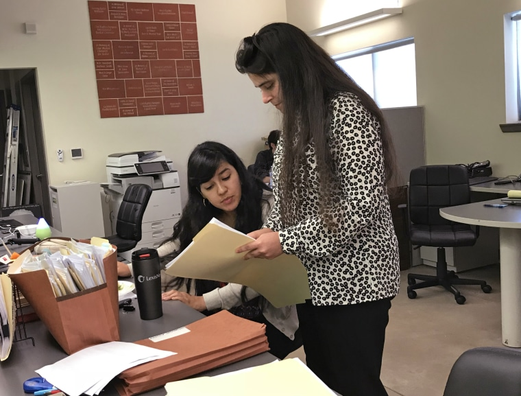 Alexis Bay, standing, and Priscilla Mendoza, law clerks at the Texas Civil Rights Project in Alamo, Texas, check details Monday in the file of a child they have been trying to locate for a father since May 29.