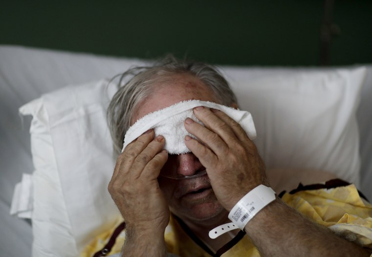 Image: A man places a cold compress on his forehead while battling the flu