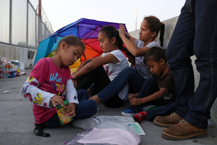 Image: A Honduran family seeking asylum wakes up on the Mexican side of the Brownsville-Matamoros International Bridge after spending the night there because U.S. Customs and Border Protection officers denied them entry near Brownsville