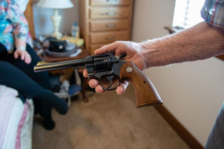 Delmar Scroughams holds a gun from his collection on May 2, 2018.