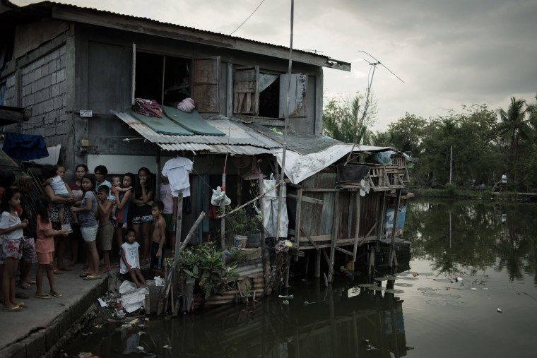 Image: Neighbors watch as the suspect is led away out the cluster of slums in Malolos, in the Philippines