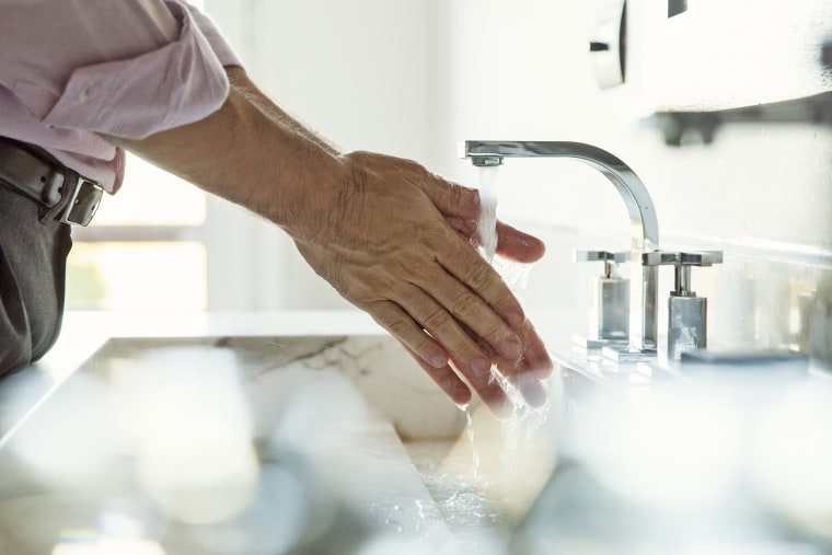 Image: Man washing hands in bathroom sink, cropped
