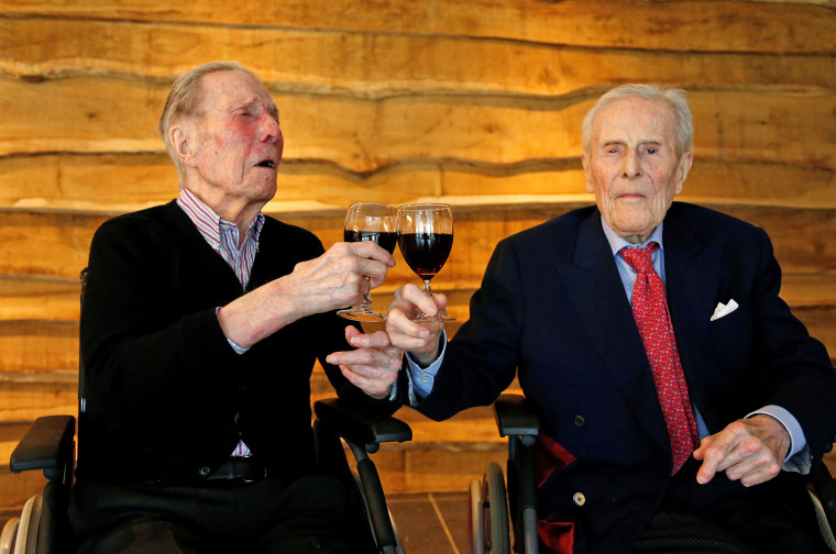 The world's oldest living twin brothers, Paulus and Pieter Langerock from Belgium, 102, toast with a glass of red wine at the Ter Venne retirement home in Sint-Martens-Latem