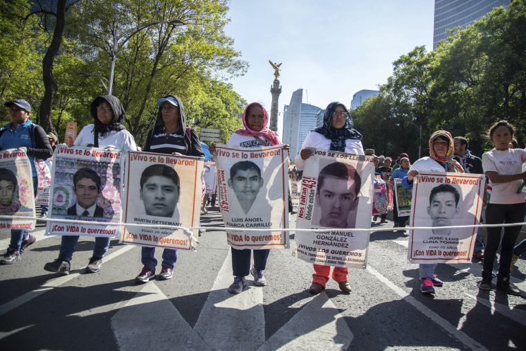 Image: Women march holding banners that show some of the faces of 43 students who went missing nearly four years ago
