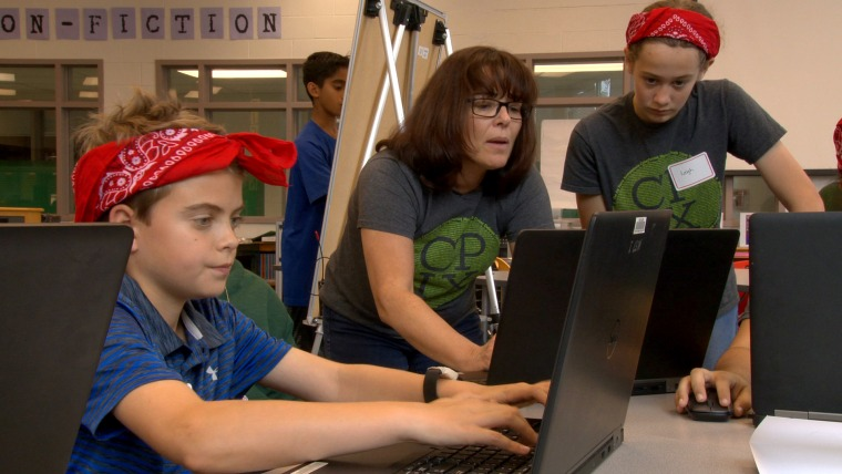 CyberPatriot competitors James Henry and Leigh Black with their coach Susie Suchodolski at Kilmer Middle School in Vienna, Virginia.