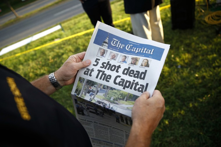 Image: A man holds a copy of The Capital Gazette newspaper