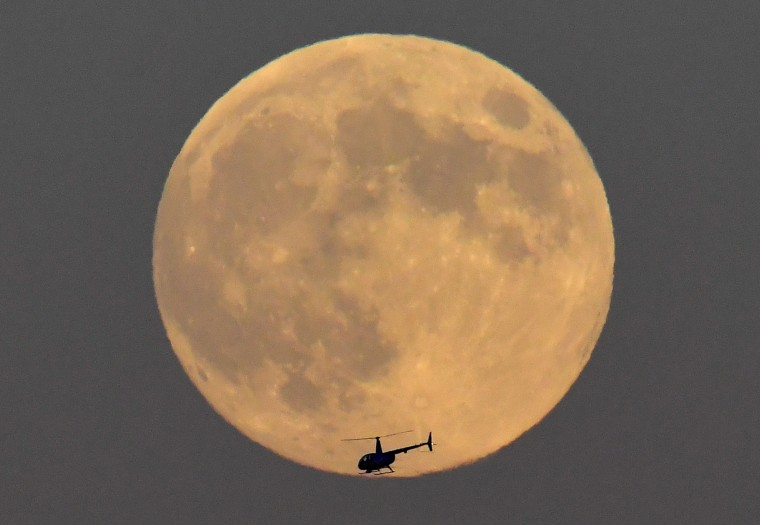 Image: A helicopter is seen passing in front of the moon, typically called a 'Strawberry Moon' when full in June, above London, Britain
