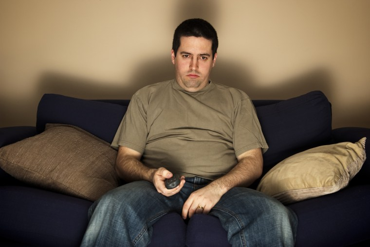 Image: Bored, lazy, overweight man sits on the sofa