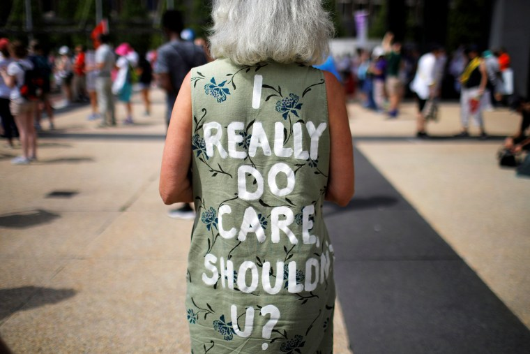 "Image: A demonstrator wears a dress reading ""I Really Do Care, Shouldn't U ?"", referencing the coat recently worn by First Lady Melania Trump, during the ""Families Belong Together"" rally in Boston"