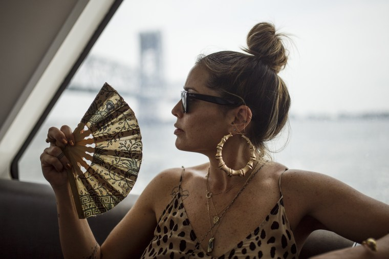 Image: A woman fans herself to keep cool on the ferry en route to Rockaway Beach