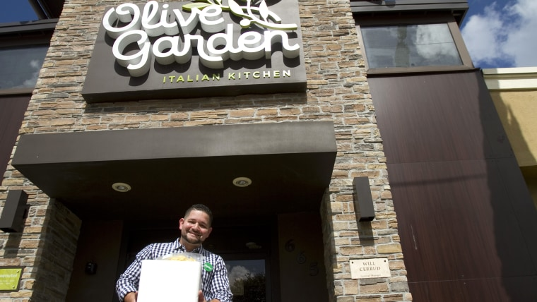 Will Cerrud in front of Olive Garden holding food to be donated.