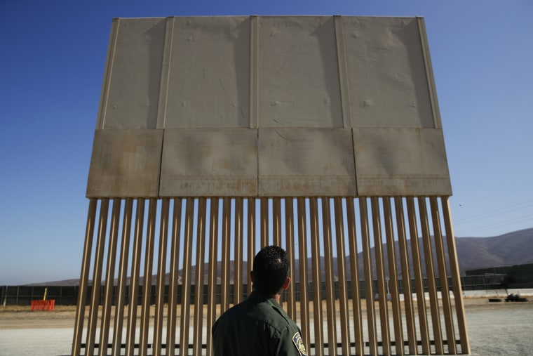 Image: A U.S. Border Patrol agent looks at one of border wall prototypes