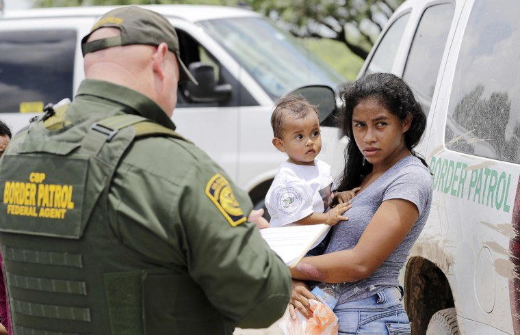 Image: A mother holds her 1-year-old child as they surrender to Border Patrol