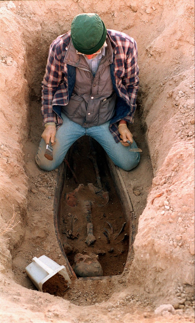 An archaeologist dusts off the remains of one of 13 Chinese men in 1996