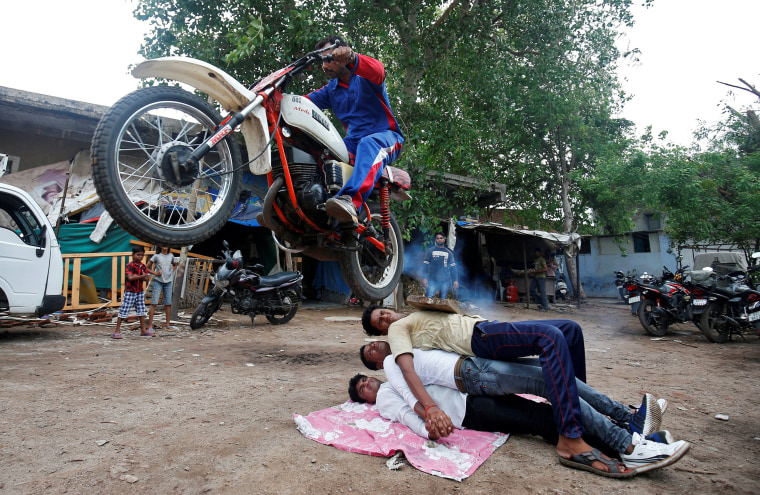 Image: A Hindu devotee performs a stunt with his motorcycle during rehearsals ahead of the annual Rath Yatra, or chariot procession, in Ahmedabad