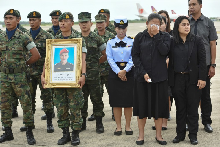 Image: An honour guard hold up a picture of Samarn Kunan as family members weep at an airport in Rayong province