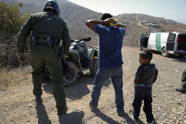 Image: A Guatemalan father and son, who crossed the U.S.-Mexico border illegally, are apprehended by a U.S. Border Patrol agent