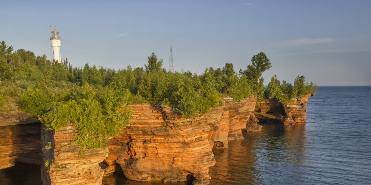 Layered sandstone cliffs and sea caves at sunrise on Devils Island in Apostle Islands National Lakeshore, Wisconsin, USA