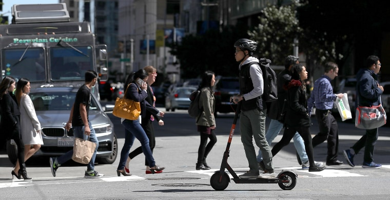 A user rides a Spin scooter in San Francisco