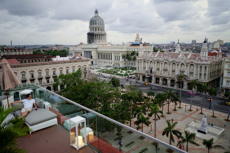 Image: A tourist enjoys a rooftop of a recently renovated Belle Epoque shopping mall housing the Gran Hotel Manzana in the top floors and luxury stores on the ground floor in Havana