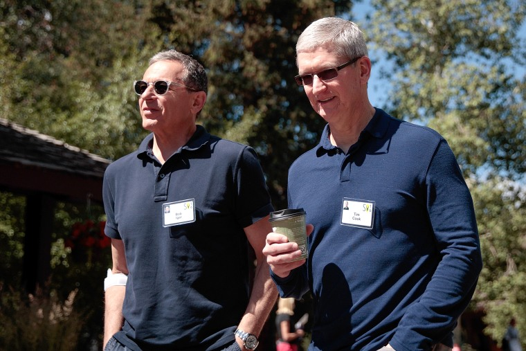 Image: Bob Iger, chief executive officer of The Walt Disney Company, walks with Tim Cook, chief executive officer of Apple Inc.