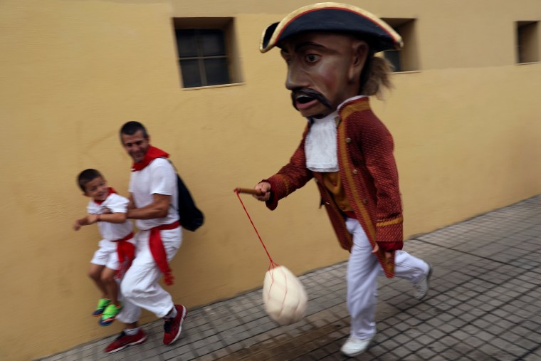 """Image: Revellers dodge a \""""Kiliki\"""" ready to hit with his sponge during San Fermin festival's \""""Comparsa de gigantes y cabezudos\"""" (Parade of the Giants and Big Heads) in Pamplona"""