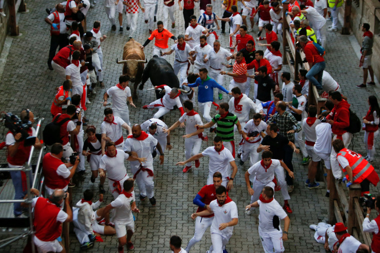 Image: Runners sprint in front of bulls during the fourth running of the bulls of the San Fermin festival in Pamplona