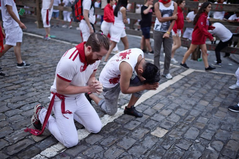 Image: Runners pray before the bull run on the fourth day of the San Fermin festival in Pamplona