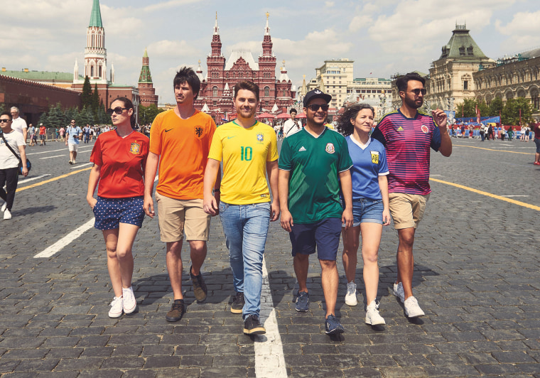 Image: Gay rights activists, wearing soccer jerseys to form a rainbow flag, walk in Red Square in Moscow