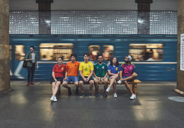 Image: Gay rights activists, wearing soccer jerseys to form a rainbow flag, sit on a bench in the metro in Moscow