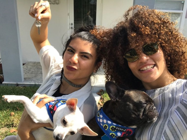 Christian Portilla (left) holds the keys to her new home in Miami, Florida while posing next to her wife, Melani Liriano, and their two dogs.