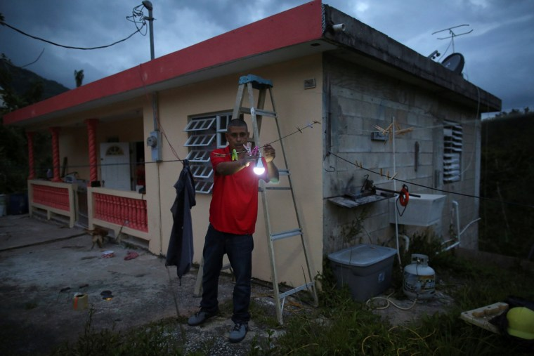 Image: Wilson Reyes attaches a solar lamp to a clothes line outside his home, as his neighbourhood is still without power nine months after Hurricanes Irma and Maria battered the island, in Adjuntas