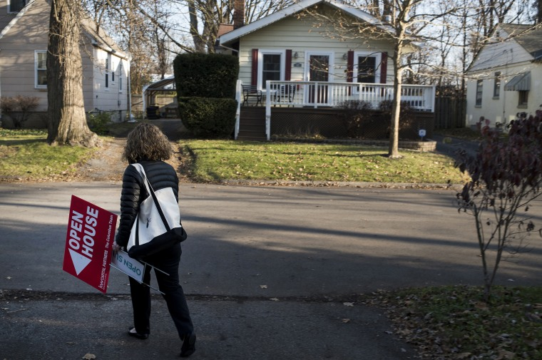 "Image: A real estate agent removes an ""Open House\"" sign displayed in the front yard of a home for sale in Columbus"