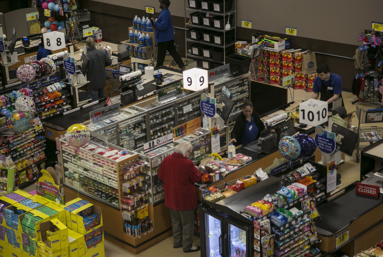 Image: Employees ring customers up at registers at a grocery store in Birmingham