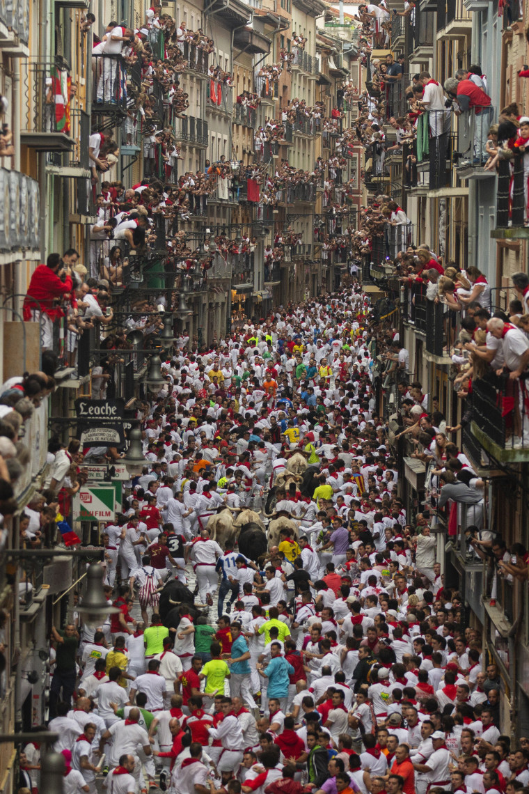 Image: Revelers run with bulls through a narrow street on the second day of the San Fermin festival
