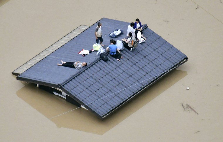 Image: People wait to be rescued from a house almost submerged in floodwaters