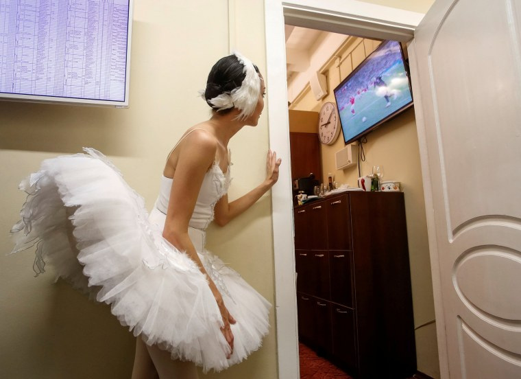 Image: A ballerina watches the broadcast of the World Cup quarter-final match between Russia and Croatia