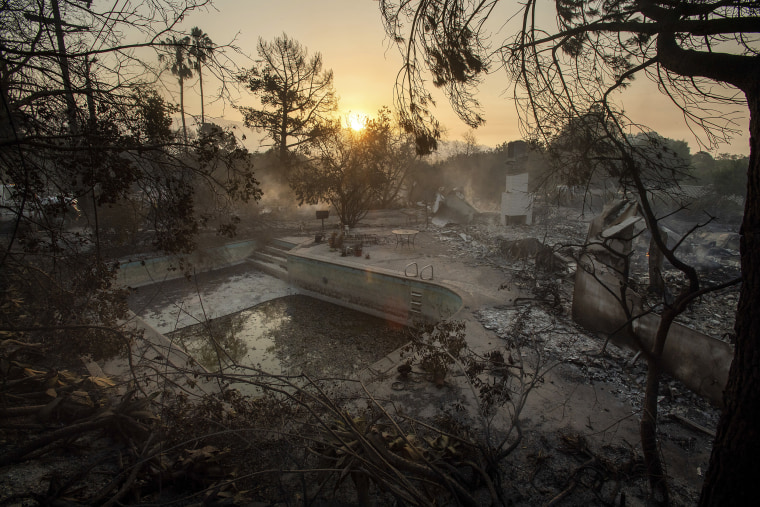 Image: The sun rises behind a home leveled by the Holiday fire in Goleta, California
