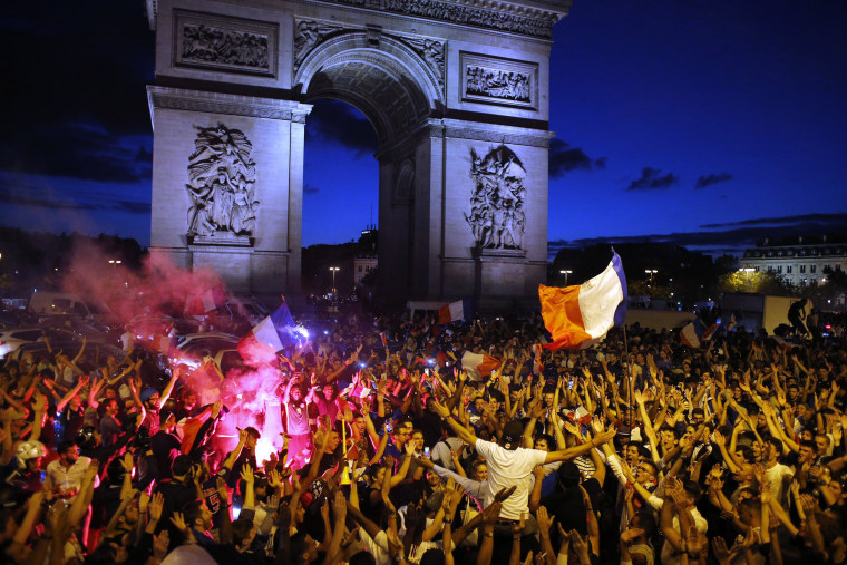 Image: People celebrate along the Champs Elysees avenue after the World Cup semifinal match between France and Belgium